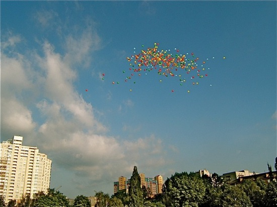 balloons flying in the sky over a festival